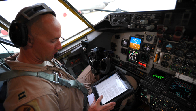 Capt. Brett Pierson, a pilot with the 340th Expeditionary Air Refueling Squadron at a non-disclosed base in Southwest Asia, refers to a computer tablet during preflight checks aboard a KC-135 Stratotanker aircraft bound for a refueling mission in Afghanistan, May 8, 2011, in support of Operation Enduring Freedom. The Hanscom Collaboration and Innovation Center at Hanscom AFB, Mass., is working with industry to provide Air Mobility Command pilots with hardened digital tablets, which can withstand digital attack and electronic interference during flight, replacing hundreds of pages of printed material with secure electronic flight bags.